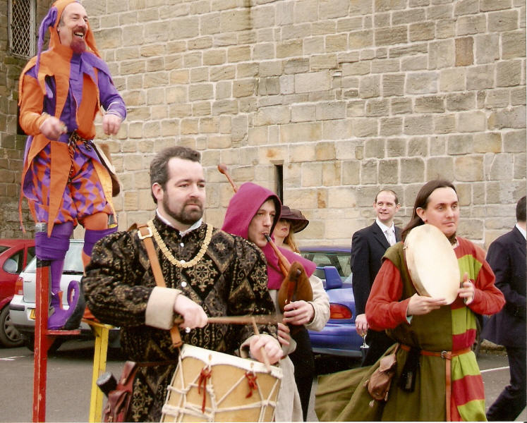 Medieval jester and musicians entertain at a wedding